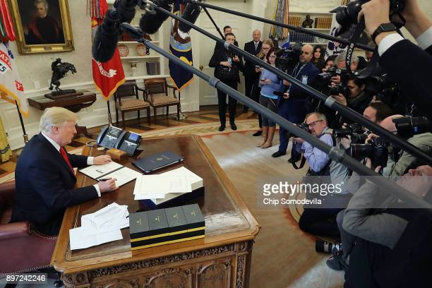 S President Donald Trump signs sweeping tax reform legislation into law in the Oval Office December 22 2017 in Washington DC Trump praised Republican...