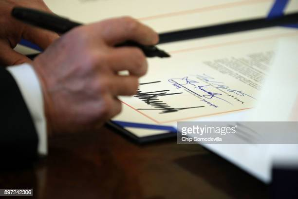 S President Donald Trump signs sweeping tax reform legislation into law in the Oval Office at the White House December 22 2017 in Washington DC Trump...