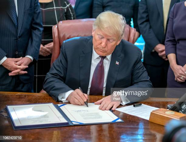US President Donald Trump signs the Cybersecurity and Infrastructure Security Agency Act in the Oval Office of the White House on November 16 2018 in...