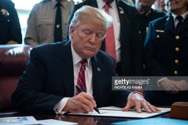 US President Donald Trump signs the first veto of his presidency overriding a congressional resolution to secure emergency funds to build his...