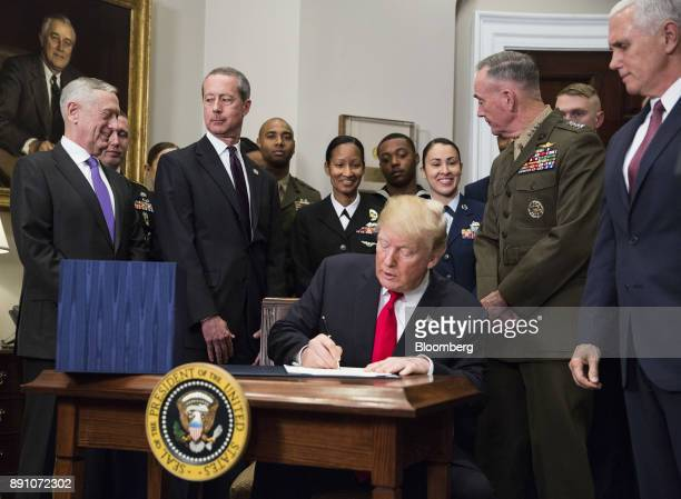US President Donald Trump signs the National Defense Authorization Act for fiscal year 2018 in the Roosevelt Room of the White House in Washington DC...
