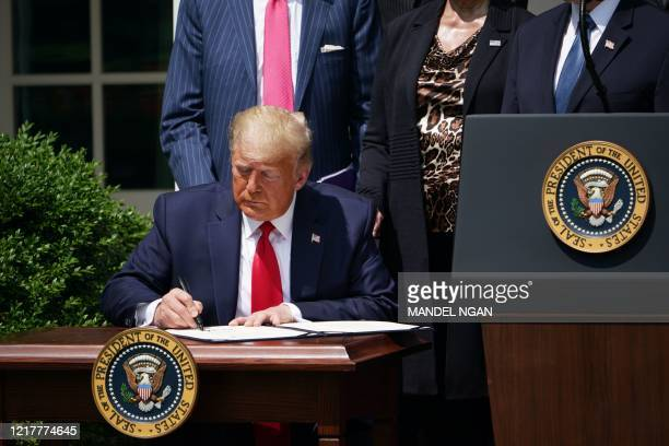 US President Donald Trump signs the Paycheck Protection Program Flexibility Act of 2020 as he holds a press conference on the economy in the Rose...