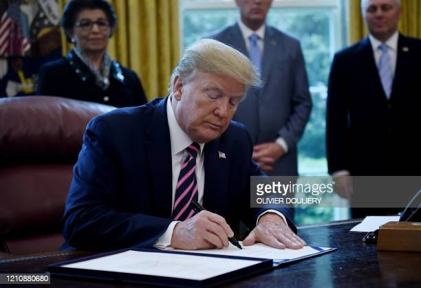 US President Donald Trump signs the Paycheck Protection Program and Health Care Enhancement Act in the Oval Office of the White House in Washington...