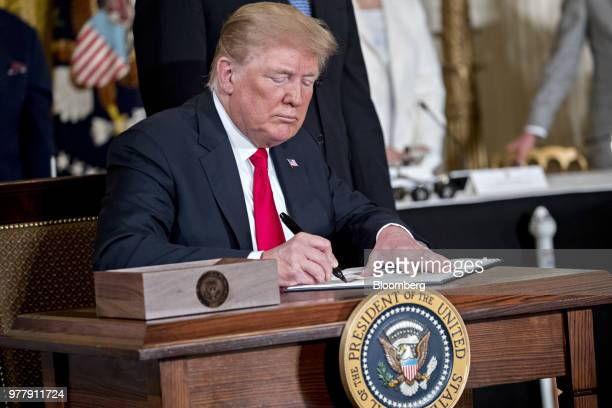 US President Donald Trump signs the Space Policy Directive3 during a National Space Council meeting in the East Room of the White House in Washington...