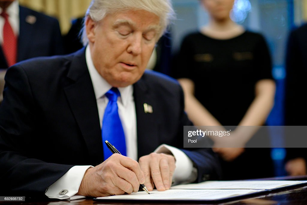 President Donald Trump signs three executive actions in the Oval Office on January 28, 2017 in Washington, DC. The actions outline a reorganization of the National Security Council, implement a five year lobbying ban on administration officials and a lifetime ban on administration officials lobbying for a foreign country and calls on military leaders to present a report to the president in 30 days that outlines a strategy for defeating ISIS.