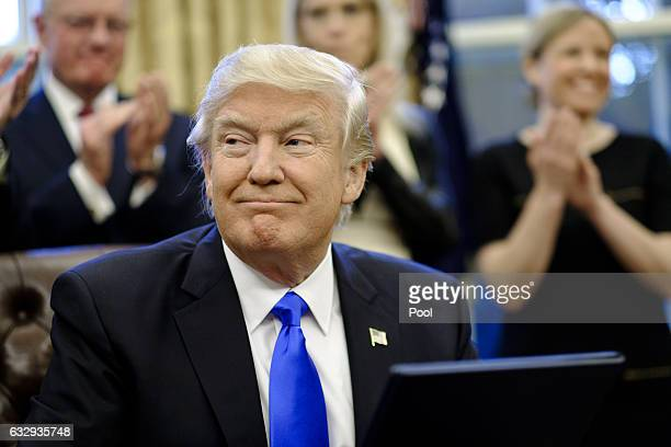 President Donald Trump signs three executive actions in the Oval Office on January 28 2017 in Washington DC The actions outline a reorganization of...