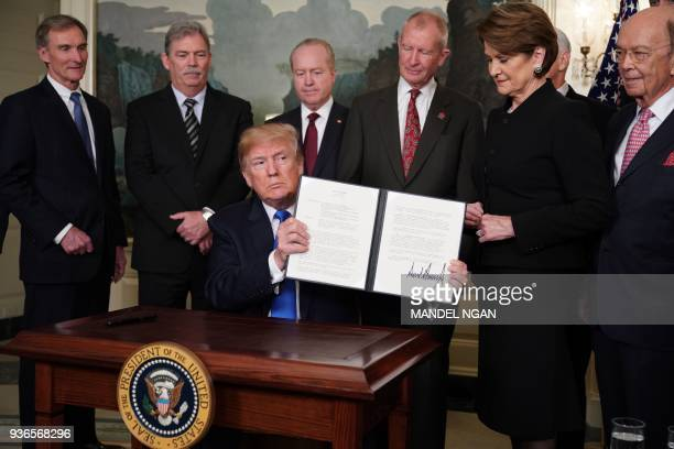 President Donald Trump signs trade sanctions against China on March 22 in the Diplomatic Reception Room of the White House in Washington, DC, on...