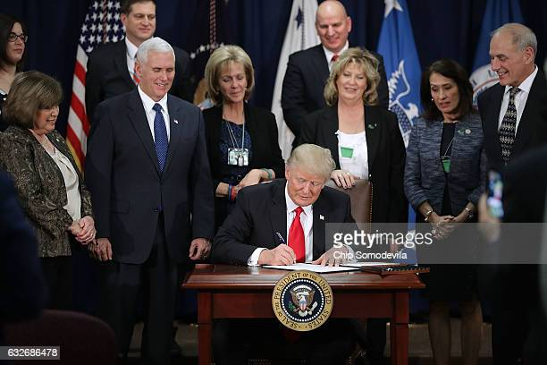 US President Donald Trump signs two executive orders during a visit to the Department of Homeland Security with Vice President Mike Pence Homeland...