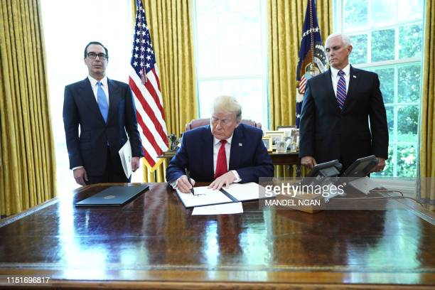 President Donald Trump signs with US Vice President Mike Pence and US Secretary of Treasury Steven Mnuchin at the White House on June 24...