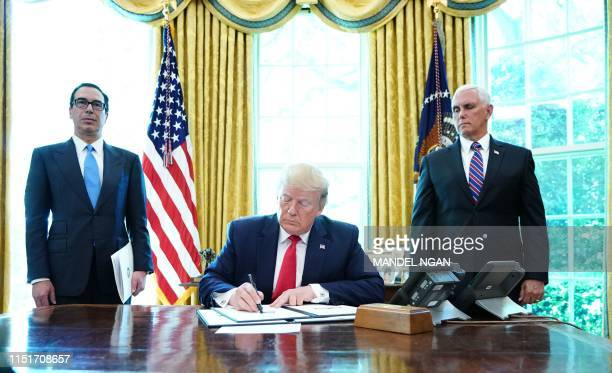 US President Donald Trump signs with US Vice President Mike Pence and US Secretary of Treasury Steven Mnuchin at the White House on June 24...