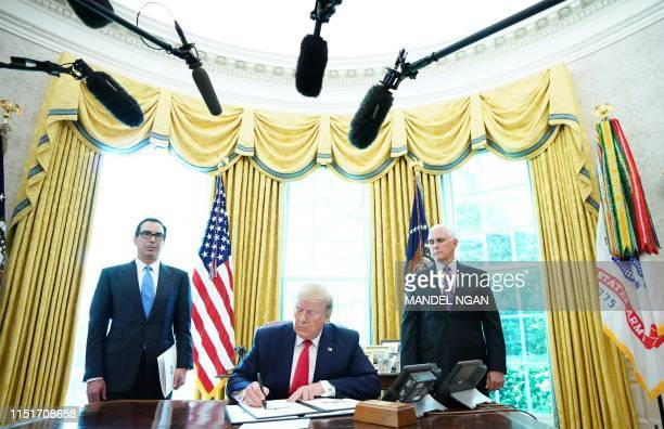 President Donald Trump signs with US Vice President Mike Pence and US Secretary of Treasury Steven Mnuchin at the White House on June 24 'hardhitting...