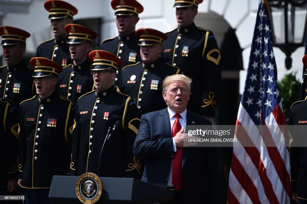 US President Donald Trump sings the National Anthem in the 'Celebration of America' at the White House in Washington, DC, on June 5, 2018. - Trump's 'The Celebration of America' honors football fans and not the NFL champions Philadelphia Eagles after he reignited his feud with the league by abruptly canceling a White House reception for the Super Bowl winners over players who kneel during the national anthem to protest social injustice.