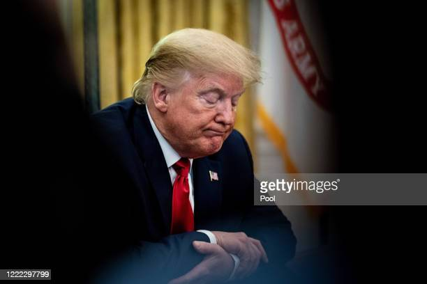 President Donald Trump sits a the Resolute Desk while announcing that the Food and Drug Administration issued an emergency approval for the antiviral...