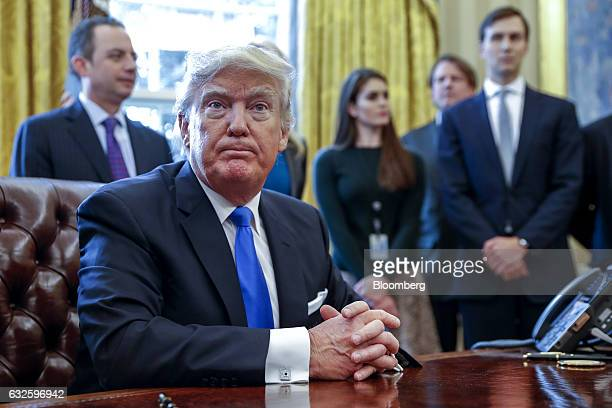 US President Donald Trump sits after signing one of five executive orders related to the oil pipeline industry in the Oval Office of the White House...