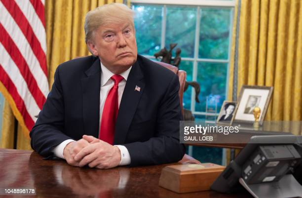 President Donald Trump sits at the Resolute Desk during a briefing on Hurricane Michael in the Oval Office of the White House in Washington, DC,...