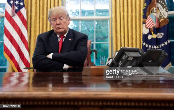 US President Donald Trump sits at the Resolute Desk during a briefing on Hurricane Michael in the Oval Office of the White House in Washington DC...