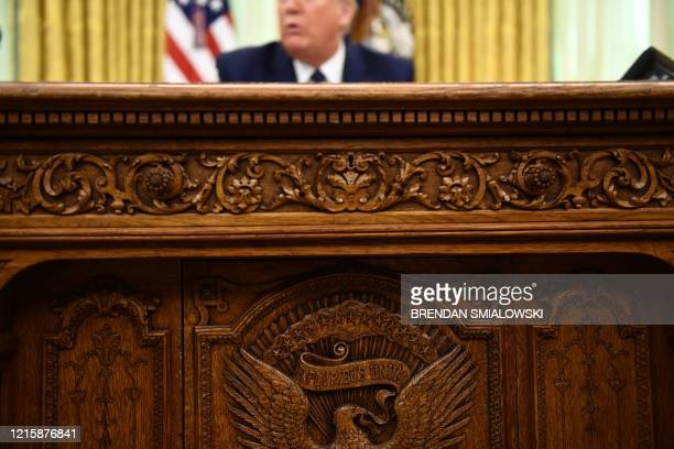 President Donald Trump sits behind the Resolute desk before signing an executive order on social-media companies in the Oval Office of the White...
