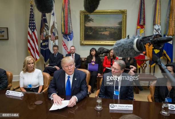 US President Donald Trump sits between Paula White of the New Destiny Christian Center and Executive Vice President and CEO of the National Rifle...