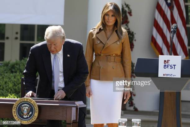 US President Donald Trump sits down as First Lady Melania Trump stands during a 'Be Best' initiative event in the Rose Garden of the White House in...