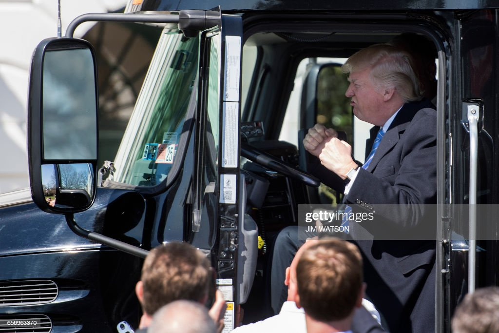 US President Donald Trump sits in the drivers seat of a semi-truck as he welcomes truckers and CEOs to the White House in Washington, DC, March 23, 2017, to discuss healthcare. /