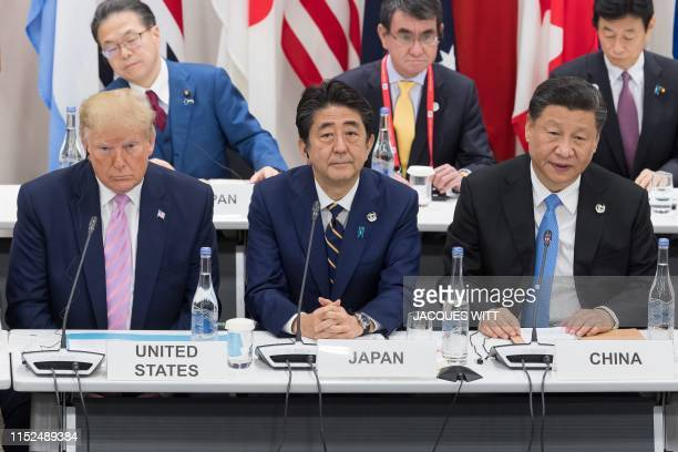 US President Donald Trump sits with Japan's Prime Minister Shinzo Abe and China's President Xi Jinping as they attend a meeting on the digital...