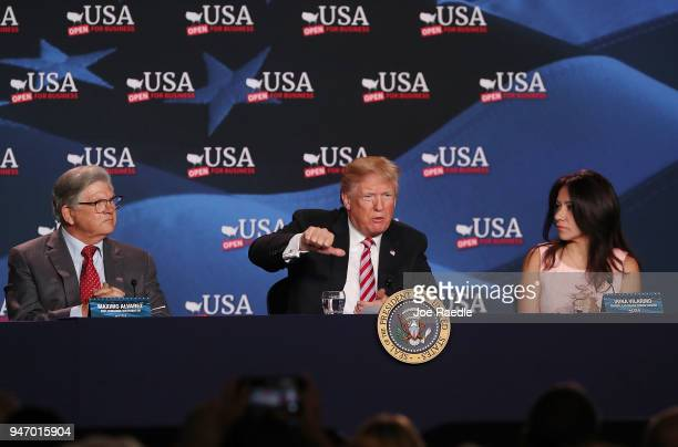 President Donald Trump sits with Maximo Alvarez and Irina Vilatino during a roundtable discussion about the Republican $15 trillion tax cut package...