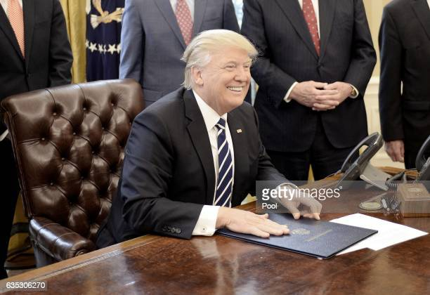 US President Donald Trump smiles after signing HJ Res 41 in the Oval Office of the White House on February 14 2017 in Washington DC The resolution...