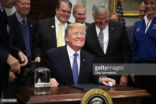 S President Donald Trump smiles after signing 'Space Policy Directive 1' during a cereomny in the Roosevelt Room at the White House December 11 2017...
