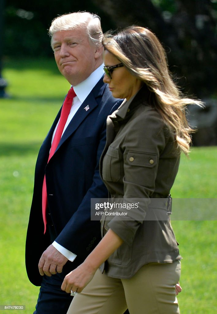 US President Donald Trump smiles as he and First Lady Melania Trump depart the White House, September 15, 2017, in Washington, DC. / AFP PHOTO / Mike Theiler