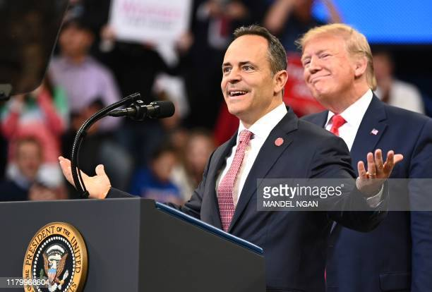 US President Donald Trump smiles behind Kentucky Governor Matt Bevin during a rally at Rupp Arena in Lexington Kentucky on November 4 2019