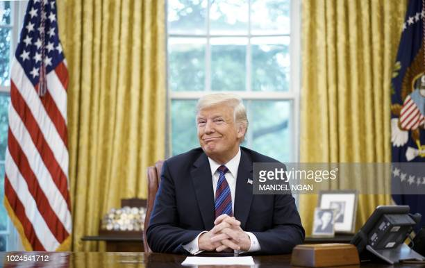 US President Donald Trump smiles during a phone conversation with Mexico's President Enrique Pena Nieto on trade in the Oval Office of the White...