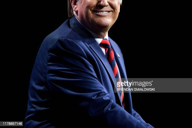 US President Donald Trump smiles while speaking during the International Association of Chiefs of Police Annual Conference and Exposition at the...