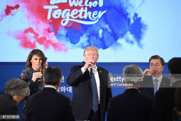US President Donald Trump South Korea's President Moon JaeIn and US First Lady Melania Trump take a drink during a state dinner at the presidential...