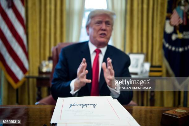 US President Donald Trump speaks about a tax reform bill after he signed it in the Oval Office of the White House December 22 2017 in Washington DC /...