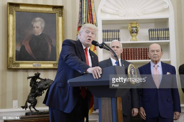 S President Donald Trump speaks about trade as Vice President Mike Pence and Secretary of Commerce Wilbur Ross look on before signing Executive...