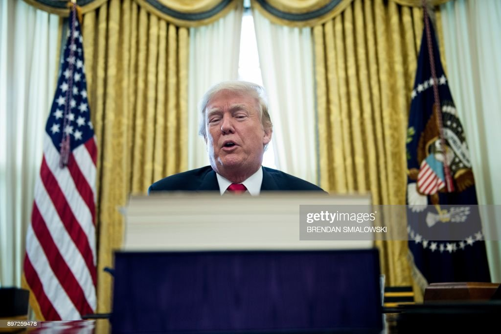 US President Donald Trump speaks after signing a tax reform bill in the Oval Office of the White House December 22, 2017 in Washington, DC. / AFP PHOTO / Brendan Smialowski