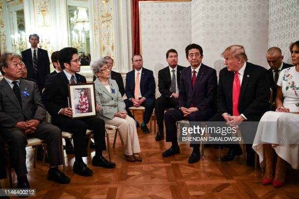 President Donald Trump speaks as First Lady Melania Trump and Japan's Prime Minister Shinzo Abe listen during a meeting with families who have had...