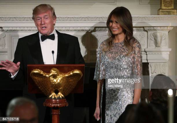 President Donald Trump speaks as first lady Melania Trump listens during a reception at the State Dining Room of the White House September 14, 2017...