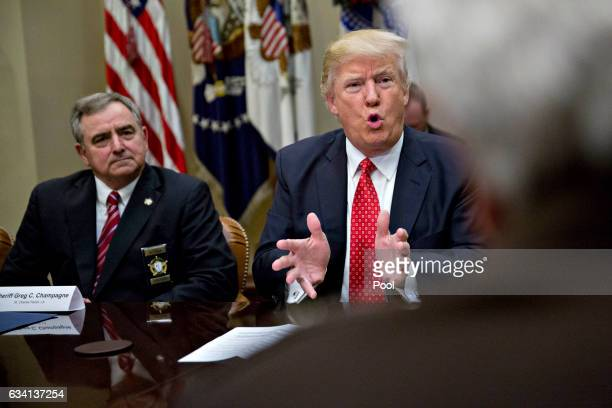 US President Donald Trump speaks as Greg Champagne sheriff from St Charles Parish Louisiana left listens during a listening session in the Roosevelt...