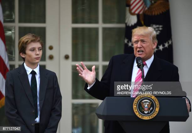 US President Donald Trump speaks as his son Barron looks on before a turkey pardoning ceremony at the White House in Washington DC on November 21...
