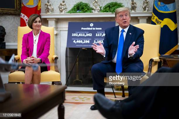 US President Donald Trump speaks as Kim Reynolds governor of Iowa left listens during a meeting in the Oval Office of the White House in Washington...