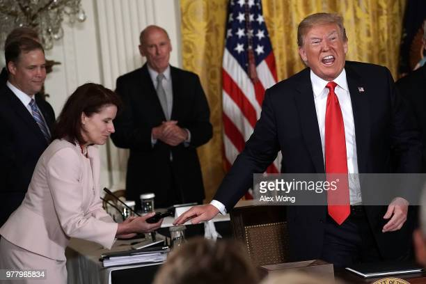 S President Donald Trump speaks as NASA Administrator Jim Bridenstine looks on during a meeting of the National Space Council at the East Room of the...