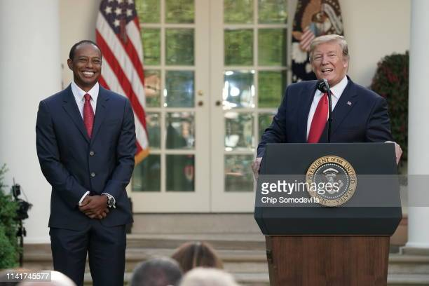 S President Donald Trump speaks as professional golfer and business partner Tiger Woods looks on during the Medal of Freedom ceremony in the Rose...