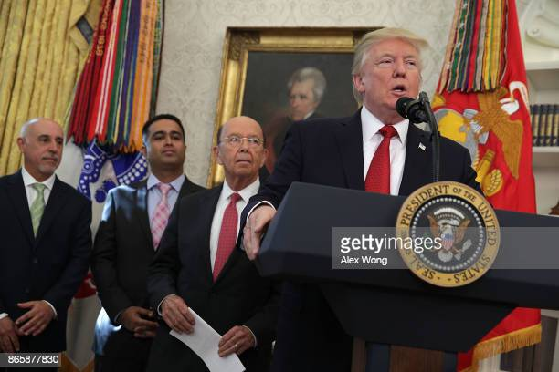 S President Donald Trump speaks as Secretary of Commerce Wilbur Ross listens during an event in the Oval Office of the White House October 24 2017 in...