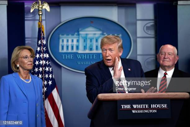 S President Donald Trump speaks as Secretary of Education Betsy DeVos and Secretary of Agriculture Sonny Perdue look on during a briefing on the...