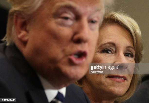 US President Donald Trump speaks as Secretary of Education Betsy DeVos listens during a parentteacher conference at the Roosevelt Room of the White...