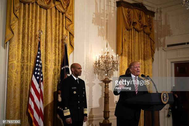 S President Donald Trump speaks as Surgeon General Jerome Adams looks on during a reception in the East Room of the White House February 13 2018 in...