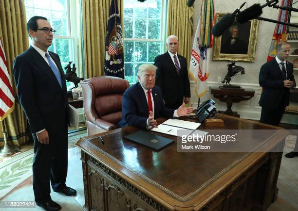 S President Donald Trump speaks as Vice President Mike Pence and Treasury Secretary Steve Mnuchin look on after the signing of an executive order...