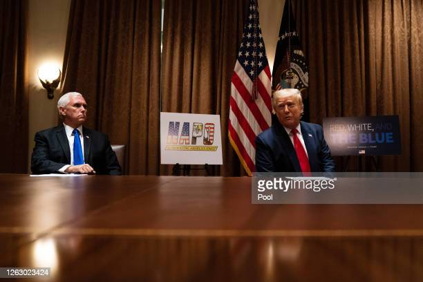 S President Donald Trump speaks as Vice President Mike Pence listens during a meeting with members of the National Association of Police...
