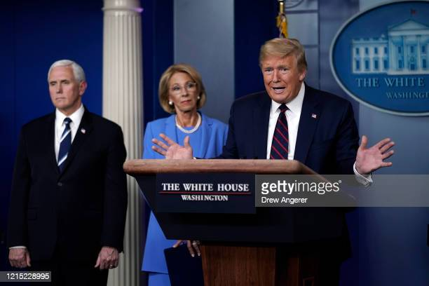 President Donald Trump speaks as Vice President Secretary of Education Betsy DeVos and Secretary of Agriculture Sonny Perdue look on during a...